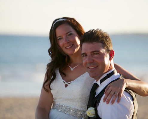 bride and groom pose for beach wedding photo