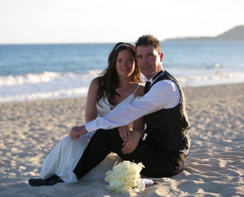 bride and groom sit together on sandy beach