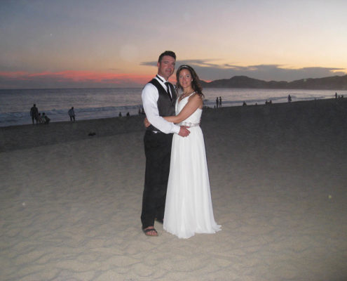 bride and groom pose on beach at sunset in Cabo, Mexico