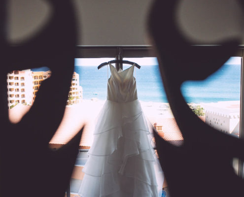wedding dress hanging up with beach and ocean behind it.