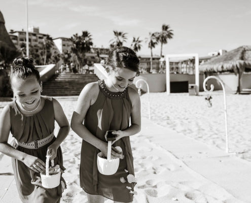 bride's maids showering petals on beach