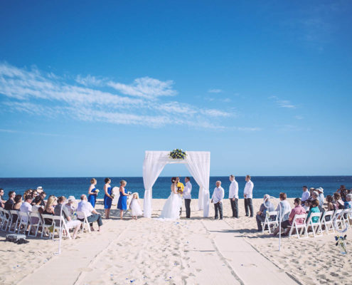wedding ceremony on beach with guests and ocean in background in Cabo, Mexico