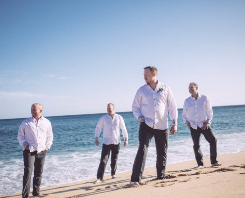 Groom and his party stand on beach