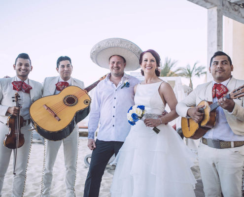 bride and groom smile with Mexican musicians in background