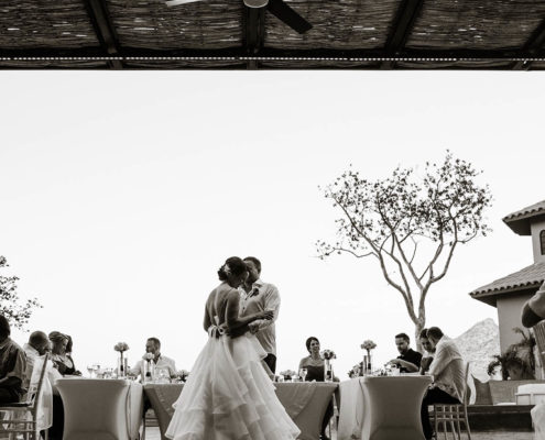 newly married couple dance in front of wedding guests