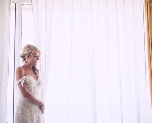 bride waiting by window before ceremony