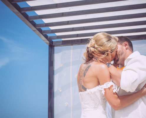bride and groom kiss under wooden canopy on beach