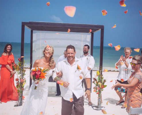 newly wed couple walking away from altar at beach wedding
