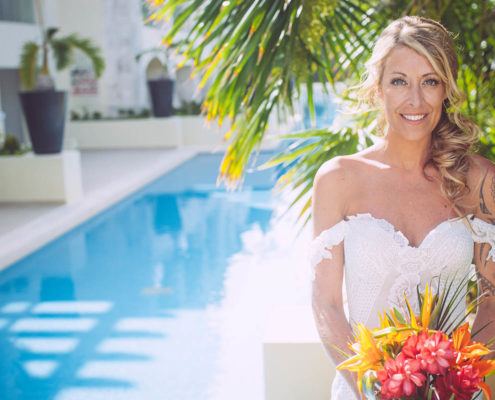 smiling bride poses with bouquet by pool