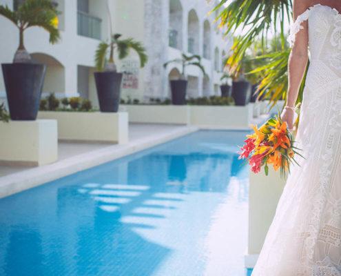 bride poses beside mexico resort swimming pool
