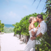 newly married couple kiss along sandy pathway