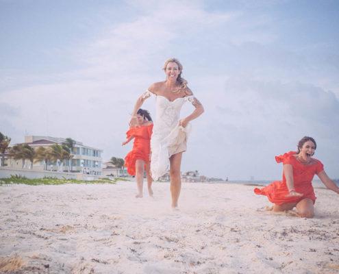 bride playfully runs along beach after wedding on white sand