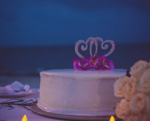 wedding cake at destination wedding in Mexico with beach in background